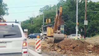A backhoe digs at a road construction site.