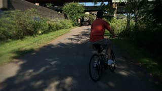 A bicyclist playfully rides his bike on a Pittsburgh bike trail.