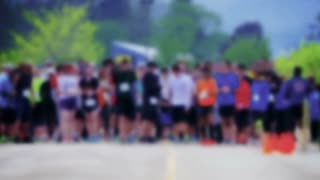 A blurred stylized shot of marathon runners at the starting line.