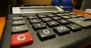 A close-up shot of an accountant entering numbers on a calculator with a pencil.