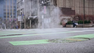 A close up shot of steam coming from a man hole cover in downtown Pittsburgh.
