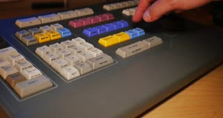 A closeup shot of a person using an edit controller to assemble video in a linear tape-based edit workstation.