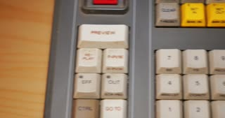 A closeup shot of an editor pressing the MARK IN and MARK OUT buttons on an edit controller in a linear tape-based edit workstation.