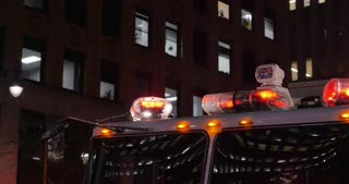 A closeup shot of the flashing red lights of a fire truck parked outside a Manhattan apartment building at night.  	Greenwich Village area
