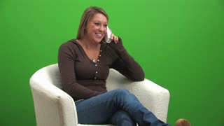A college-aged girl talks on a cordless phone. Shot over green so you can key it over your own background