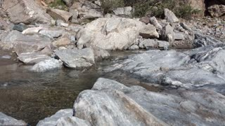 A daytime establishing shot of a small stream in the rocky Arizona desert. With audio.