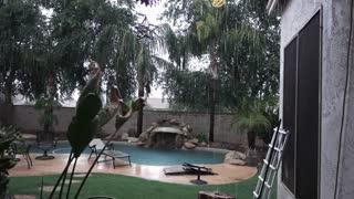 A daytime establishing shot of an Arizona residence backyard pool in a monsoon or rain storm.