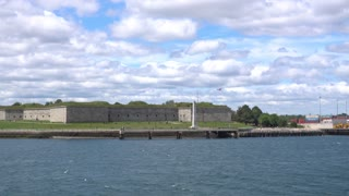 A daytime establishing shot of Castle Island Park in Boston as seen from the harbor.
