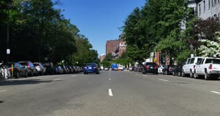 A daytime establishing shot of traffic on Boston's tree-lined Beacon Street.