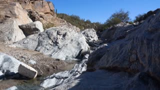 A daytime low angle establishing shot of a small stream in the rocky Arizona desert.