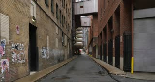 A daytime overcast DX establishing shot of an empty alley in a big city.