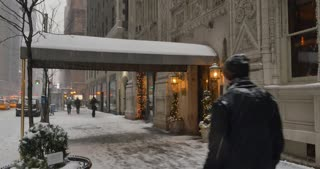 A daytime winter establishing shot of the entrance of a typical Manhattan upscale apartment building.