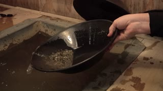 A female tourist panning for gold in an Alaskan shop.