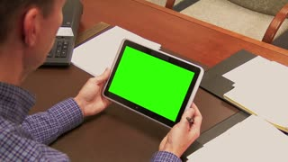 A finance officer works at his desk with a tablet PC.  Green screen tablet for custom content with luma matte and optional tracking points.