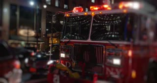 A fire truck with flashing red lights sits outside a Manhattan apartment building at night. Greenwich Village area