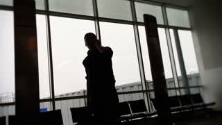A frustrated man talks on the phone after missing his flight.