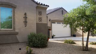 A garage door opens automatically on a home in a typical Phoenix neighborhood.