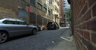 A gritty Manhattan alley dolly up establishing shot.