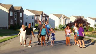 A Group of People Dance Outside in a Neighborhood