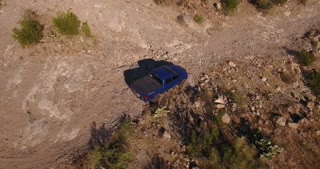 A high-angle aerial view of a single 4x4 truck off-roading in the Arizona desert.