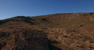 A high angle reverse aerial daytime flyover establishing shot of the Arizona desert.