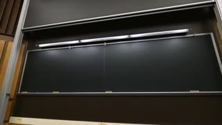 A large chalkboard lowers into place in front of a university's classroom.