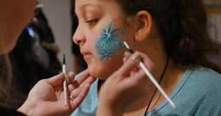A little girl gets her face painted at a carnival or craft show.