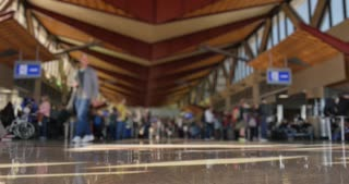 A low angle defocused shot of passengers walking around at a large airport's terminal station.