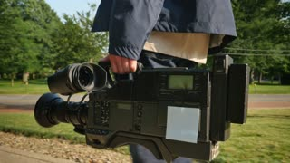 A low angle shot of a cameraman carrying his video camera to a production.  Trackable plane on camera for placement of a custom logo.