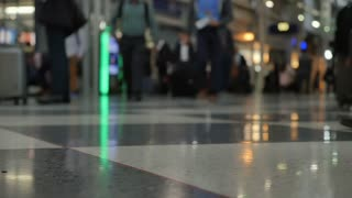 A low angle super slow motion shot of passengers walking in an airport terminal. Shallow depth of field.
