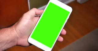 A man holds a generic smartphone in portrait mode. Green screen with optional luma matte included.