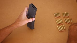 A man loads bullets into the magazine of an AR-15 rifle.