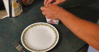 A man opens up a Chinese food container and prepares leftovers.