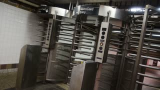A man passes through the turnstiles of a subway station in New York City.
