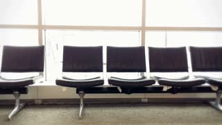 A man rests at the gate at an airport.