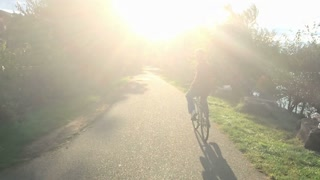 A man rides his bike into the sunset on a Pittsburgh bicycle trail. Slow motion, shot at 120fps.