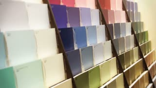 A man selects a paint sample in a big box hardware store.