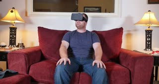 A man sitting on a sofa in his home uses a virtual reality heads up unit.