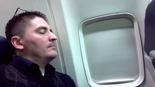 A man sleeps on a plane.