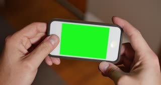 A man uses a blank green screen smartphone to play a video game. Optional corner pin markers included for advanced tracking.