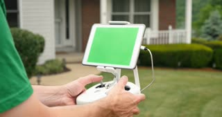 A man uses a RC controller for a drone or UAV outside a house. Green screen generic tablet with optional corner markers for advanced screen tracking.