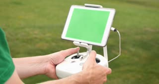 A man uses a RC controller for a drone or UAV outside in an open field. Green screen generic tablet with optional corner markers for advanced screen tracking.