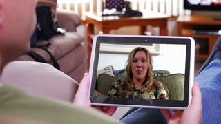 A man video chats on his tablet PC inside his home. Screen image customizable upon request.