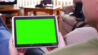 A man watches television while holding a tablet device. Screen customizable with included optional luma matte and tracking points for advanced tracking.