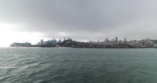 A morning establishing shot of the foggy skyline of San Francisco as seen from the Bay.