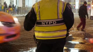 A New York City police officer helps guide traffic and pedestrians on the snowy streets of Manhattan.