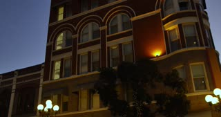 A nighttime establishing shot of a typical hotel or apartment building in a large city.