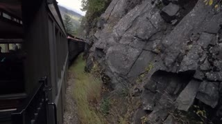 A passenger's perspective riding a train through the Rocky Mountains of Alaska.