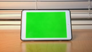 A person turns on then touches the screen of an iPad.  Green screen with luma matte for custom screen placement.