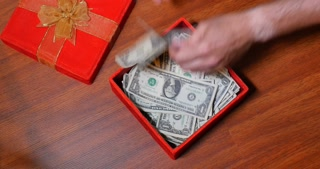 A present box reveals a hidden storage place for $1 US bills. Serial numbers on bills removed.